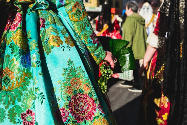 Several of the thousands of women falleras who parade down the street of la paz with their typical valencian spanish dresses during the offering