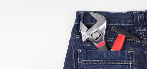 Несколько инструментов в заднем кармане из джинсовой ткани. инструменты в заднем кармане. место для вашего текста.