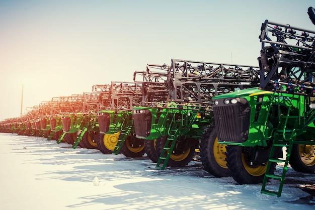 Несколько тракторов выстроились в очередь в сельскохозяйственном секторе