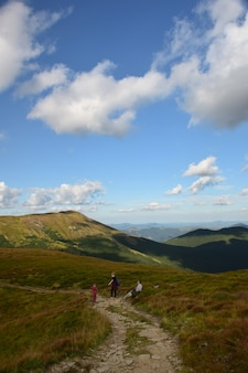 Several travelers walking along the ridge to the top of the mountain against the blue sky