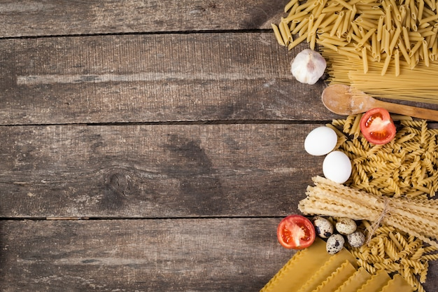 Several types of dry pasta with tomatoes.