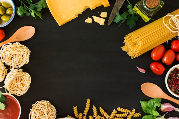 Several types of dry pasta with vegetables and herbs on black background