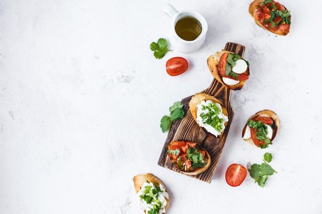 Several types of italian bruschetta with tomatoes, mozzarella and herbs on a wooden board