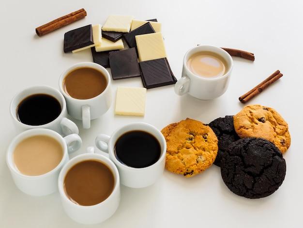 Несколько видов кофе в белых чашках. много разных сладостей.