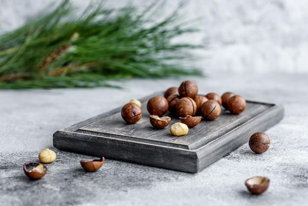 コンクリートの木製まな板にトウヒの枝を持ついくつかの種類のナッツ