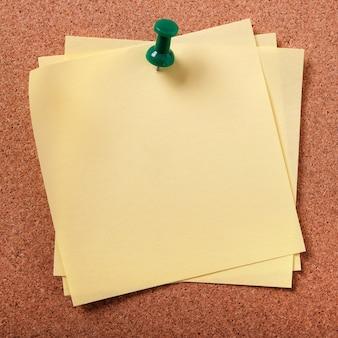 コルクボードに固定されたいくつかの乱雑な付箋紙のメモ