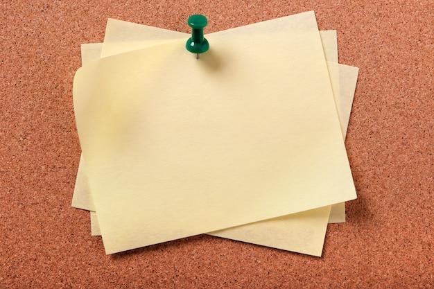 코르크 보드에 고정 된 여러 어수선한 노란색 스티커 메모 노트