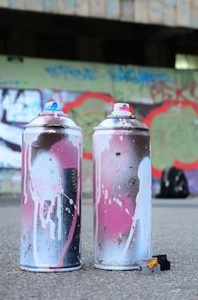 분홍색 및 흰색 페인트와 압력 하에서 페인트를 분사하기위한 캡이있는 여러 가지 스프레이 캔은 낙서 벽의 페인트 벽 근처 아스팔트에 있습니다.