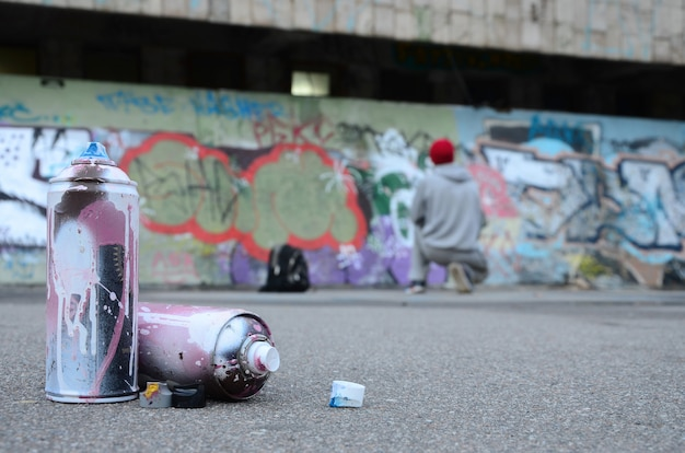 Several used spray cans with pink and white paint lie on the asphalt against the standing guy
