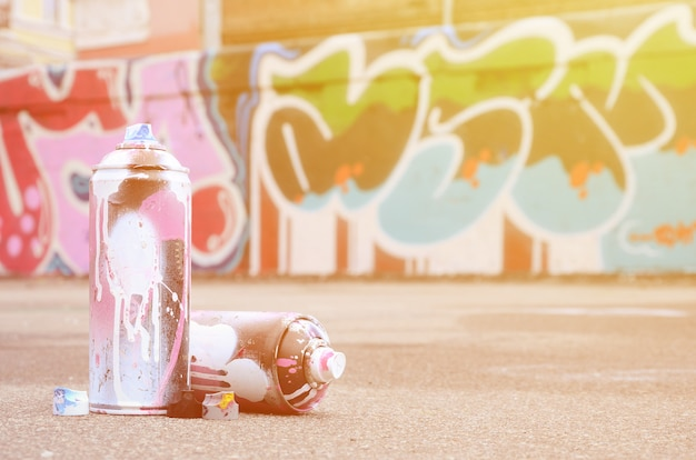Several used spray cans with pink and white paint near the painted wall in colored graffiti drawings