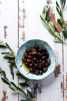 Several varieties of fresh olives in different ceramic plates on an old vintage gray napkin tablecloth table background. natural product concept. rustic vintage set of cutlery. top view, copy space