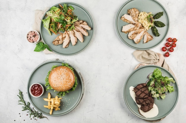 Several warm dishes with chicken, turkey, beef fillets and pork cutlet burgers in different plates served by the chef on a light background, top view with a copispace. flat lay. restaurant food.