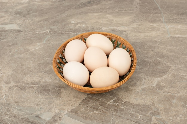 Несколько белых яиц в плетеной корзине
