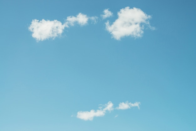 Several white fluffy beautiful clouds swim in clear blue sky in daylight