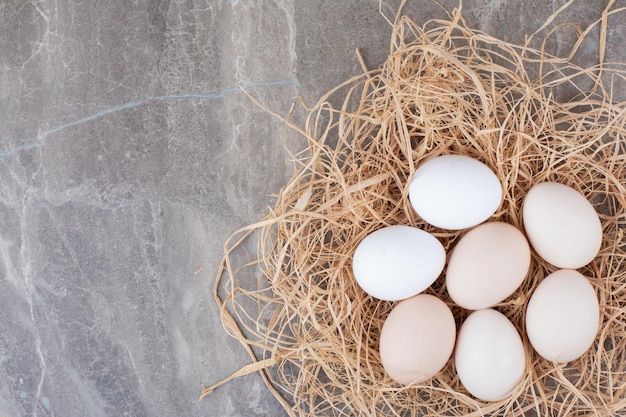 Several white fresh eggs on hay on marble background. high quality photo