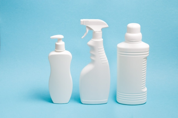 Several white plastic bottles with various types of dispensers on a blue surface