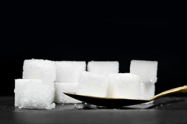 黒い石の背景に真鍮のスプーンにいくつかの白い角砂糖を入れました。