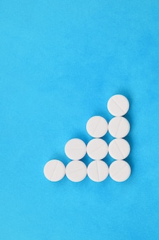 Several white tablets lie on a bright blue background