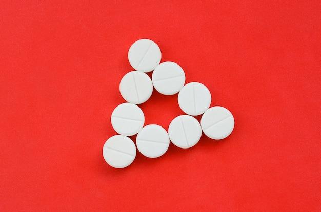 いくつかの白い錠剤は、一様な三角形の形で明るい赤の背景にあります