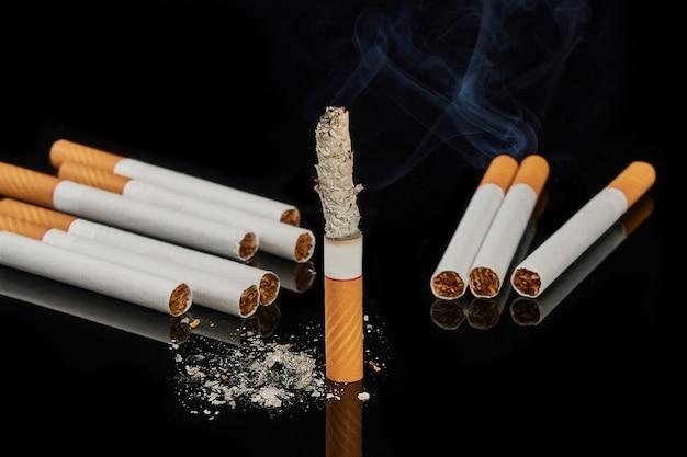 Несколько целых сигарет и одна курящая сигарета на черной поверхности