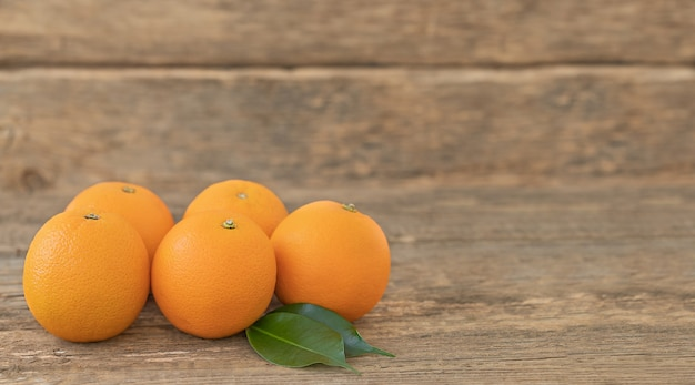 Several whole oranges with green leaves on a wooden table