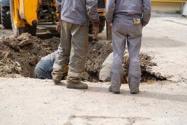 배관 문제를 해결하기 위해 구멍을 파는 작업복의 여러 작업자