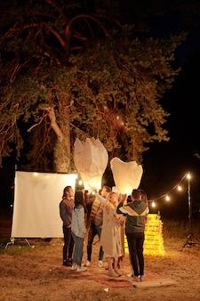 Несколько молодых веселых друзей в теплой повседневной одежде наслаждаются вечеринкой на открытом воздухе с большими белыми воздушными шарами и подсветкой