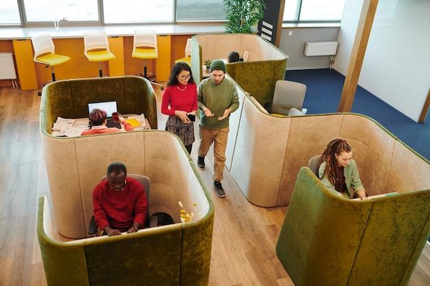 Несколько молодых межкультурных коллег в повседневной одежде сидят за столами в офисе и смотрят на дисплеи ноутбуков во время индивидуальной работы