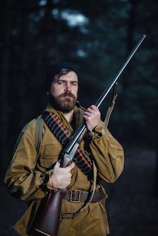 Суровый брутальный бородатый мужчина-охотник в черной шляпе и куртке цвета хаки в длинном плаще держит в руке пистолет, направленный в сторону леса