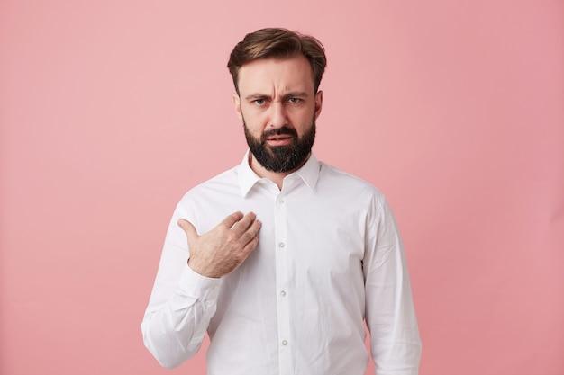 Grave giovane maschio barbuto dai capelli scuri con taglio di capelli corto che tiene il palmo sul petto e guarda confusamente davanti, sopracciglia accigliate sul muro rosa mentre indossa una camicia bianca
