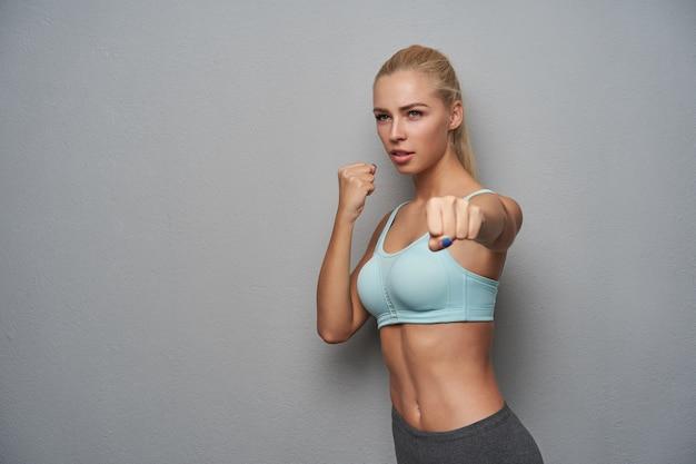 カジュアルな髪型を脇に見て、上げられた握りこぶしでボクシングをし、仕事の後にハードワークをして、明るい灰色の背景に立っている、重度のスポーティな若いブロンドの女性