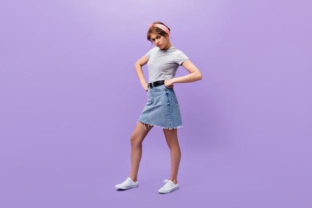 デニムスカートとグレーのシャツを着た重度の女性がカメラを覗き込む。白い流行のスニーカーのポーズで夏のヘッドバンドを持つ不満の女の子。