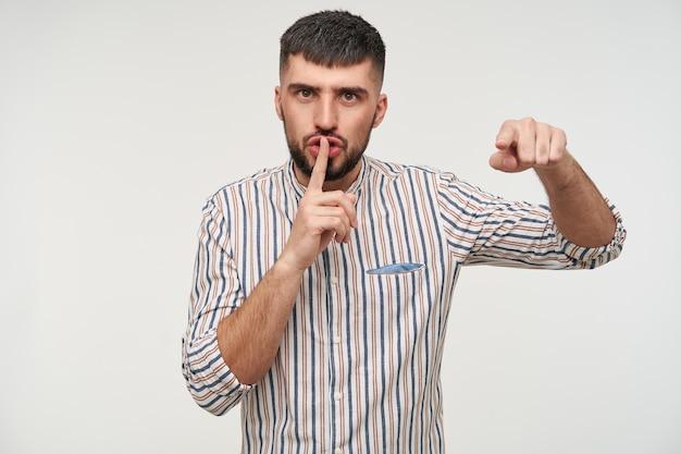 Grave giovane maschio barbuto attraente bruna che punta con la mano alzata e che tiene l'indice sulle labbra mentre guarda seriamente, in posa sopra il muro bianco
