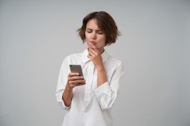 포즈를 취하는 동안 손으로 턱을 잡고 공식적인 옷을 입고 휴대 전화를 손에 들고 화면을 심각하게보고 짧은 머리를 가진 심각한 젊은 매력적인 여자