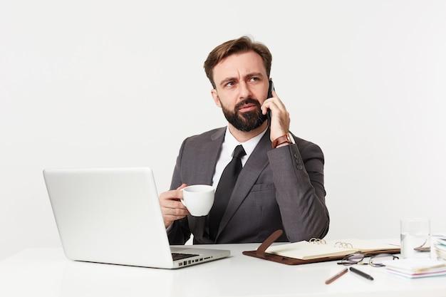 Grave giovane uomo d'affari barbuto con taglio di capelli corto e barba lussureggiante seduto al tavolo di lavoro, avendo conversazione telefonica mentre beve caffè, isolato sopra il muro bianco