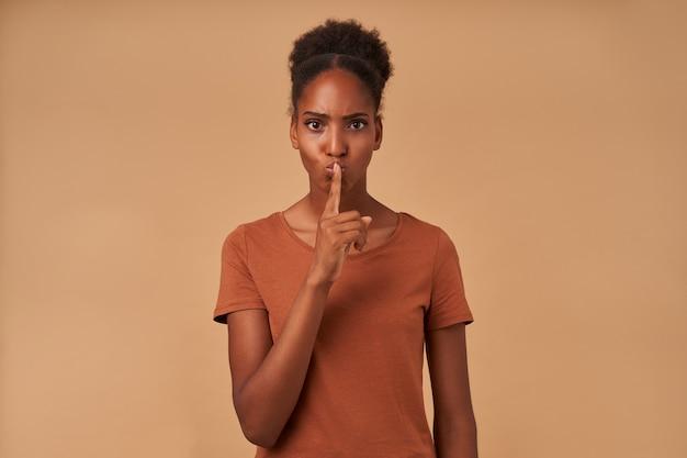 Grave giovane donna bruna riccia dagli occhi marroni con pelle scura che aggrotta le sopracciglia e solleva la mano in gesto di silenzio, in piedi sul beige