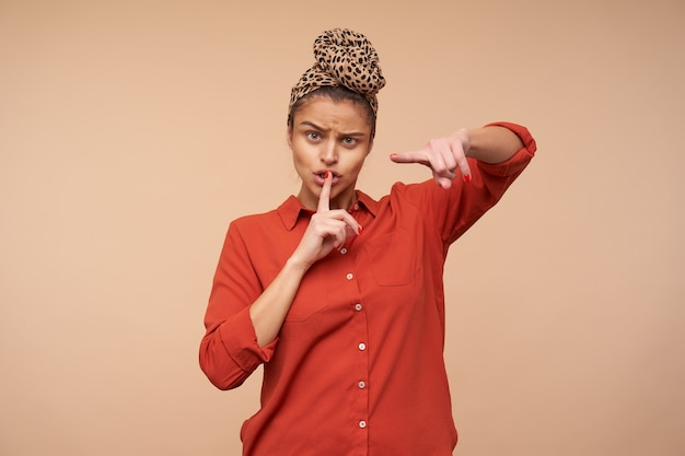 Severe young brown haired lady frowning her eyebrows and pointing at front with index finger, asking to be quiet while standing over beige wall