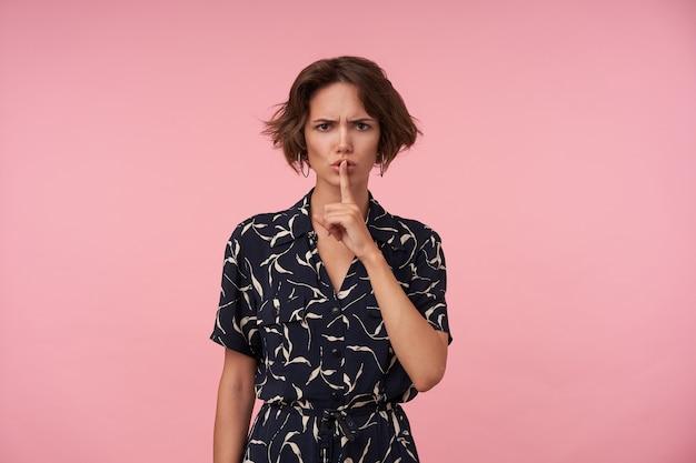 Severa giovane donna bruna con acconciatura casual in piedi in elegante abito romantico, alzando il dito indice alla bocca in gesto di silenzio