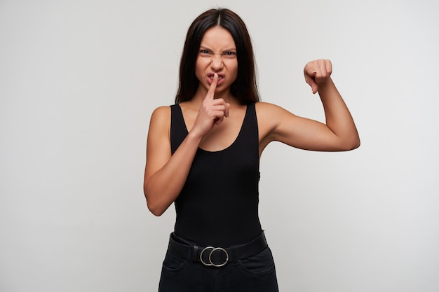 Severe young dark haired female with casual hairstyle frowning viciously her face and pointing with forefinger, asking to be quiet while standing