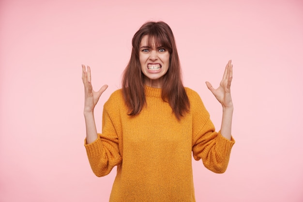 Severe young dark haired woman with casual hairstyle raising emotionally her hands while standing over pink wall, showing her white teeth while looking angrily