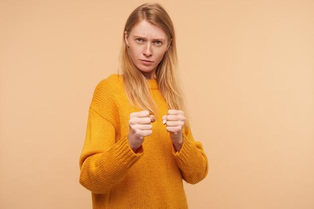 Суровая молодая зеленоглазая рыжая женщина с непринужденной прической, подняв кулаки в защитном жесте и нахмурив брови, серьезно смотрит, изолирована на бежевом