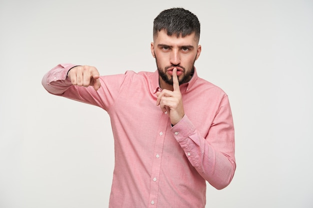 Severe young handsome short haired brunette guy with beard frowning eyebrows and raising hand with hush gesture, asking to keep silence while standing over white wall