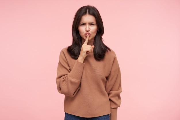 Grave giovane bella signora mora con acconciatura casual aggrottando le sopracciglia mentre guarda seriamente davanti e tenendo il dito indice sulle labbra, isolato sopra il muro rosa
