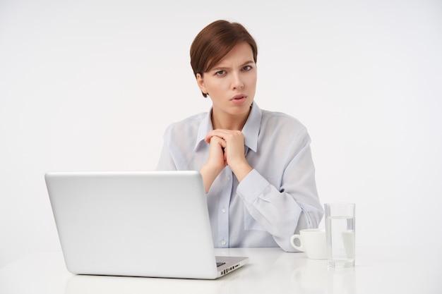 Grave giovane donna bruna dai capelli corti con trucco naturale che guarda seriamente e aggrottando le sopracciglia, piegando le mani alzate mentre è seduto su bianco