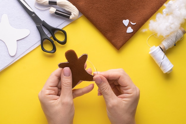 Sew two pieces of felt gingerbread man with a buttonhole stitch. step-by-step instruction . step 5.