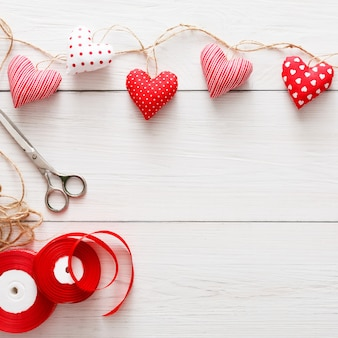 素朴な白い木の板で手作りするためのツールと赤い洗濯ばさみの境界線に枕のハートの縫い目