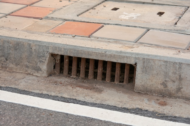 Sewer drain along road in city