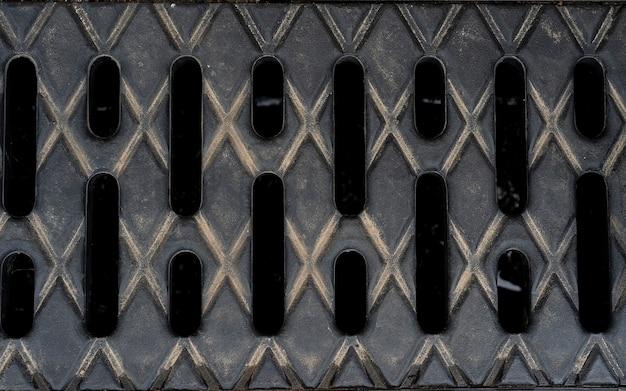 都市道路のテクスチャの下水道マンホール排水路、警告付きのマンホールカバー金属雨水管。排水システム。アイデアは家を建てることです。下水道と排水のための地面の火格子