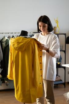 Канализационная работа с манекеном, регулирующим модный плащ на манекене портного в студии модного дизайна