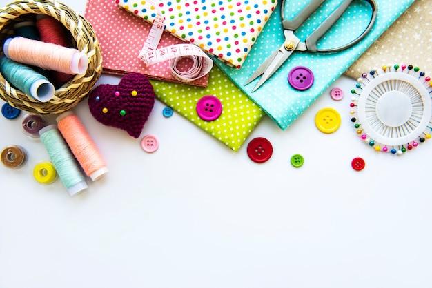 Швейная фурнитура и ткань на белом фоне. фу, плоская планировка.